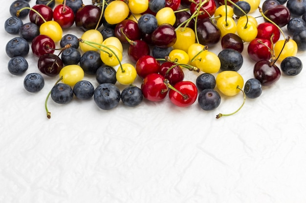 Yellow and red cherry, blueberry on white background. flat lay  copy space.