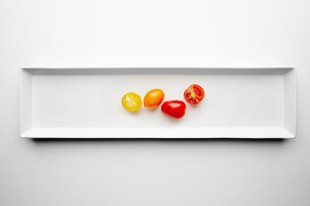 Yellow and red cherry tomatoes isolated on white plate with splitted half, top view
