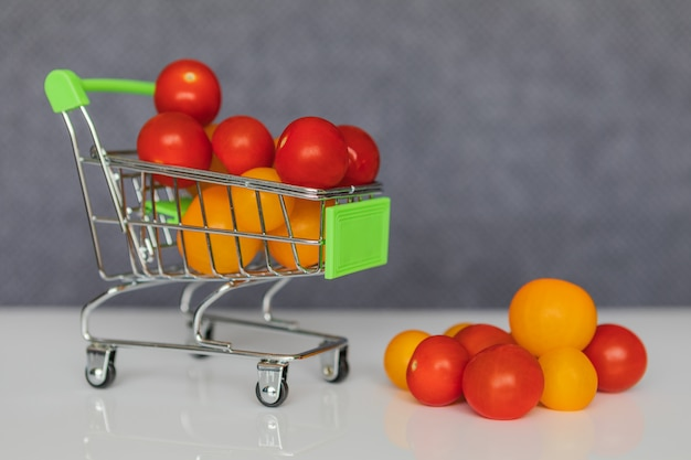 Yellow and red cherry tomatoes in a shopping cart.