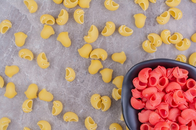 Yellow and red color pastas on the marble surface