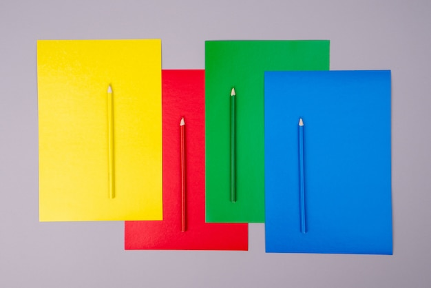 Yellow, red, green and blue pencils with colored paper on gray