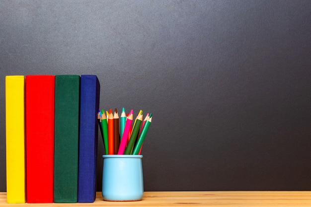 Yellow red green and dark blue books with colorful pencils in front of chalkboard. back to school concept. education background.