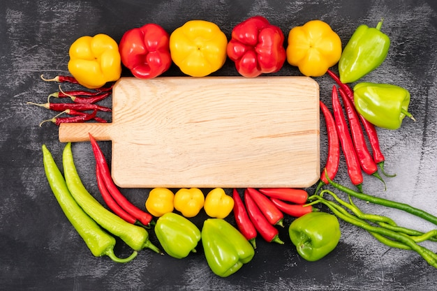 Yellow, red, green sweet pepper and chili peppers around the cutting board