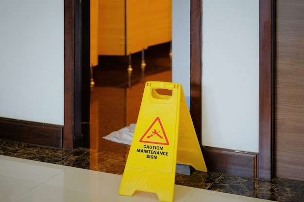 Yellow and red maintenance in progress warning sign in front of open door into a bathroom