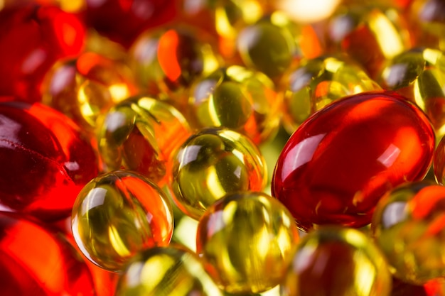 Yellow and red medical capsules on a mirror surface