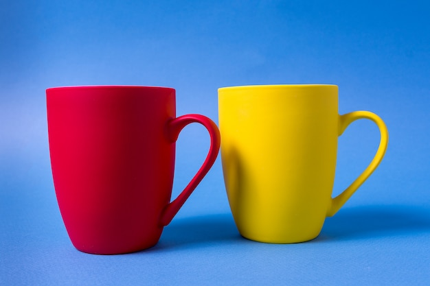 Yellow and red mugs isolated on blue background.