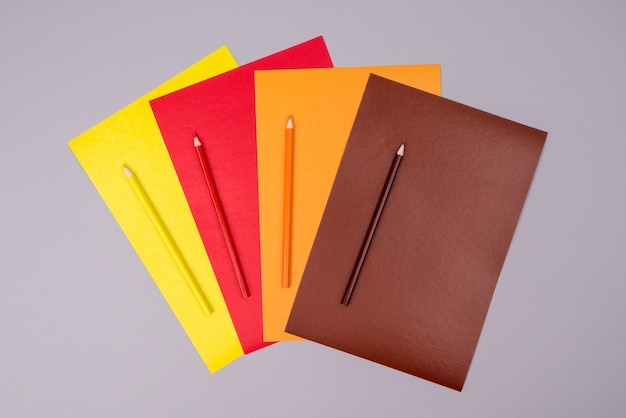 Yellow, red, orange and brown pencils with colored paper on gray