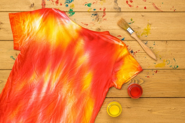 Yellow and red paint and a tie dye t-shirt on a wooden table