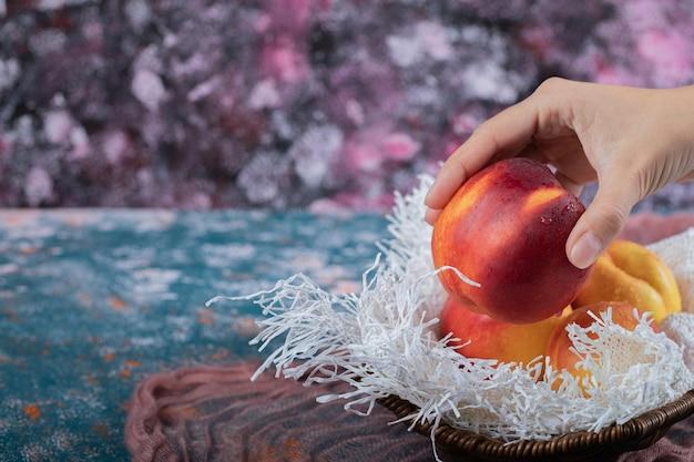 白い黄麻布の部分に木製のバスケットに黄色の赤桃。
