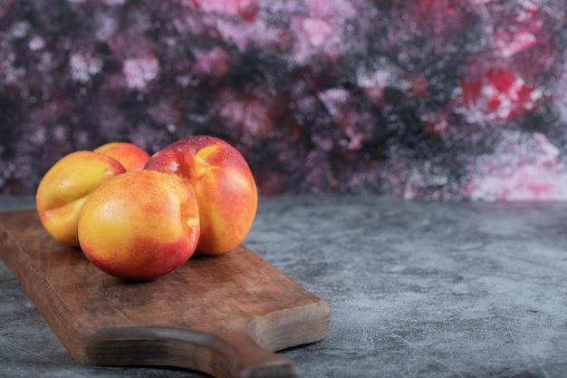 Желтые красные персики на деревянном блюде.