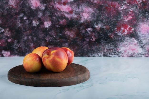 Pesche rosse gialle su una tavola di legno rustica.