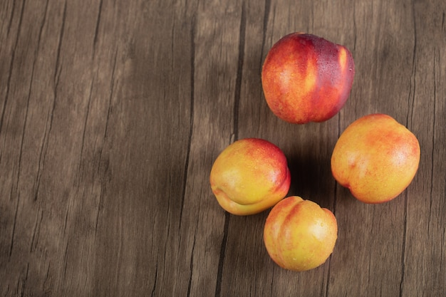 Yellow red peaches on a wooden cutting board.
