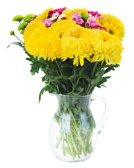 Yellow, red and pink fresh mum flowers bouquet in glass vase isolated on white background