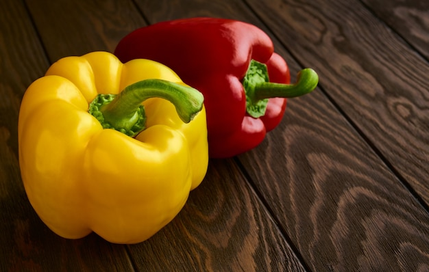 Yellow and red sweet bell peppers close up on a wooden background