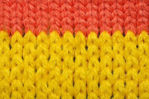 Yellow and red synthetic knitted fabric close up. knitted fabric texture. multicolor patterned knitted fabric texture. background