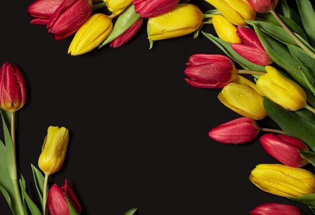 黒の背景に露の滴が付いた黄赤色のチューリップ上からの眺めはがきの場合