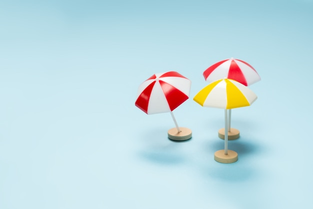 Yellow and red umbrella on a blue background. copy space.