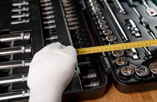 Желтая выдвижная рулетка распространяется в мужских руках в строительной перчатке над открытым набором инструментов, крупным планом.