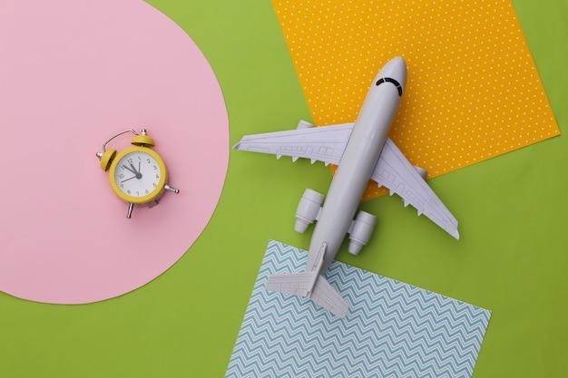창의적인 다채로운 종이 배경에 노란색 복고풍 알람 시계와 비행기. 여행 시간.