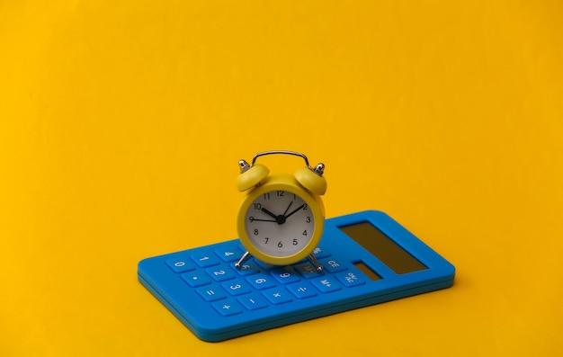 노란색 배경에 노란색 복고풍 알람 시계와 계산기.