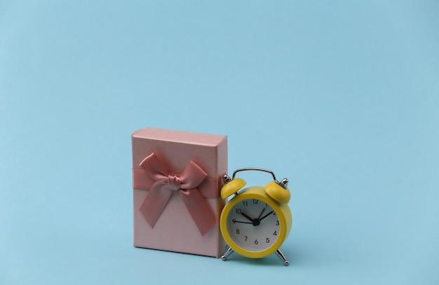 青い背景に黄色のレトロな目覚まし時計とギフトボックス。