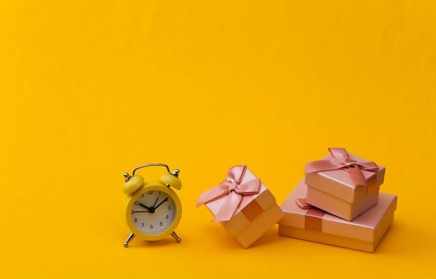 黄色のレトロな目覚まし時計と黄色の背景にギフトボックス。
