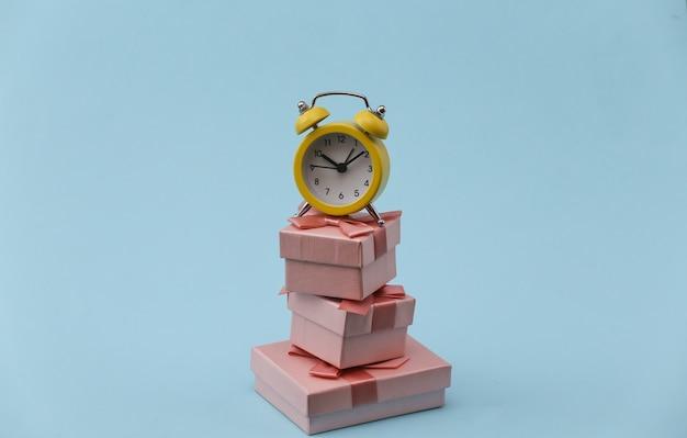黄色のレトロな目覚まし時計と青い背景の上のギフトボックスのスタック。