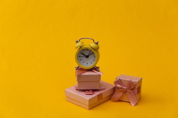 黄色のレトロな目覚まし時計と黄色の背景にギフトボックスのスタック。