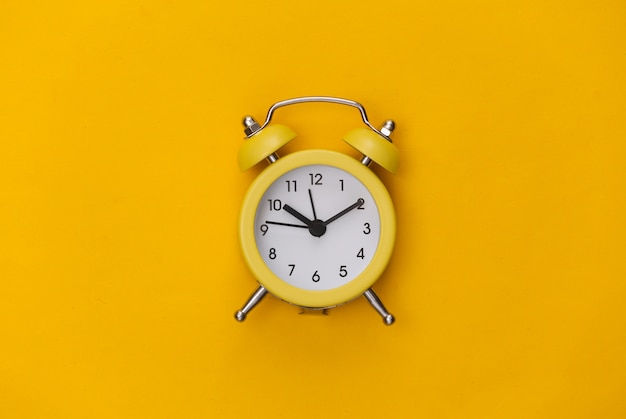 黄色の背景に黄色のレトロな目覚まし時計。 。ミニマリズム