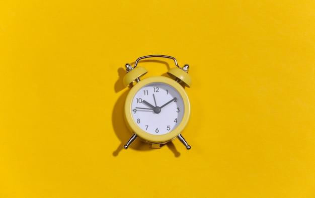 黄色の明るい背景に黄色のレトロな目覚まし時計。 。ミニマリズム