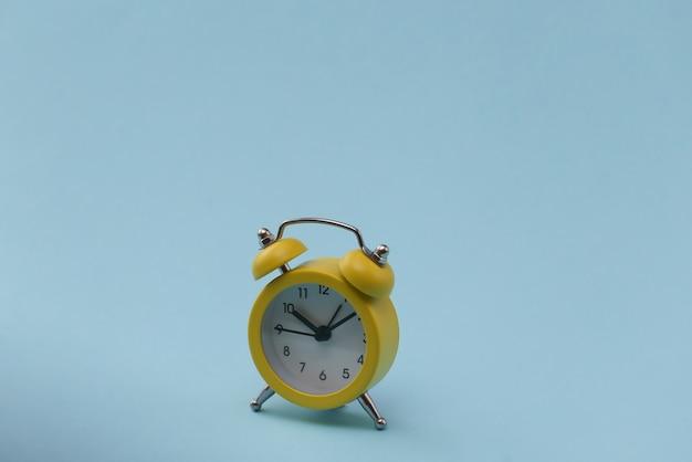 Желтый ретро будильник на синем фоне.
