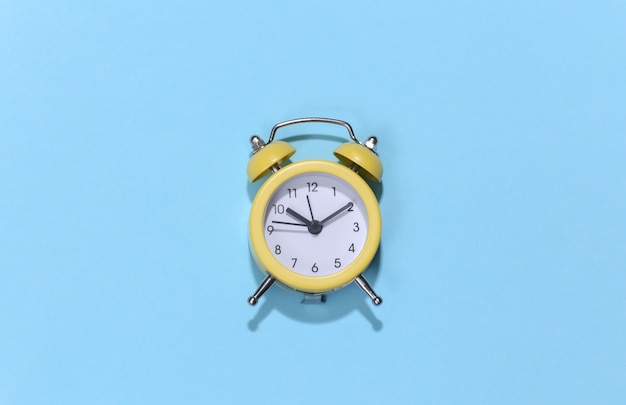 青の明るい背景に黄色のレトロな目覚まし時計。 。ミニマリズム
