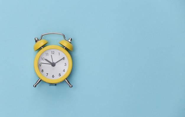 青いパステルカラーの背景に黄色のレトロな目覚まし時計。スペースをコピーします。 。ミニマリズム
