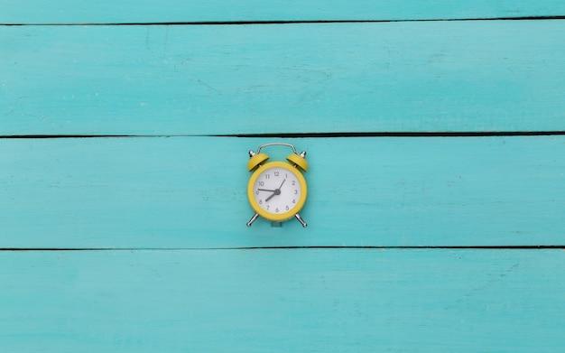 Желтый ретро будильник на синем деревянном фоне.