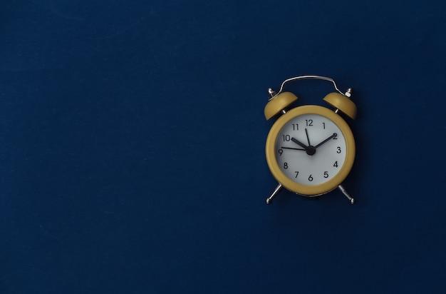 古典的な青い背景の黄色のレトロな目覚まし時計。スペースをコピーします。 。ミニマリズム