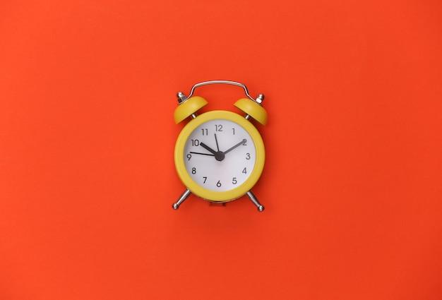 オレンジ色の明るい背景に黄色のレトロな目覚まし時計。 。ミニマリズム