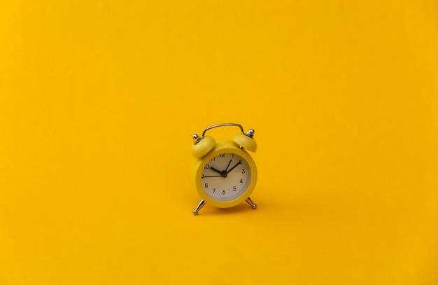 Желтый ретро будильник на желтом фоне.