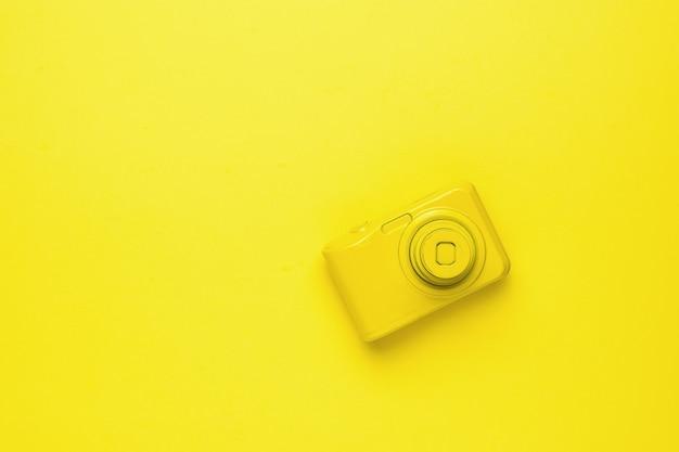밝은 노란색 배경에 노란색 복고풍 카메라입니다. 사진 장비의 흑백 이미지입니다. 플랫 레이.