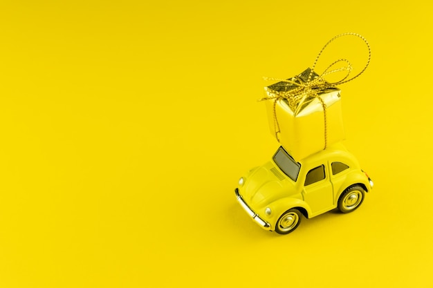 Yellow retro car with golden gift box on a roof