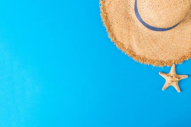 복사 공간 seastar 평면도와 노란색 복고풍 밀 짚 모자. 파란색 배경에 여름 개념입니다.