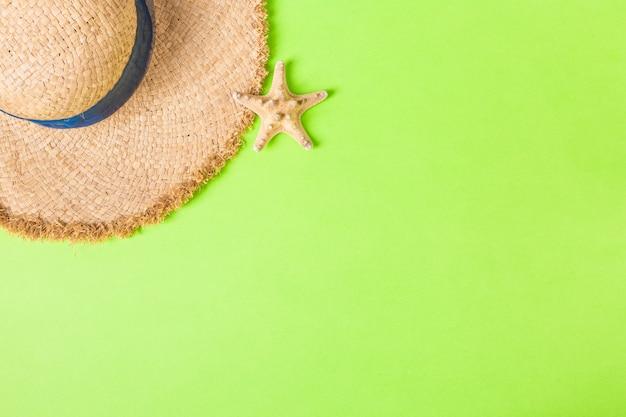 복사 공간 seastar 평면도와 노란색 복고풍 밀 짚 모자. 녹색 배경에 여름 개념입니다.