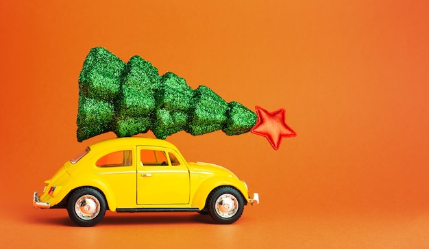 Yellow retro toy car carrying festive christmas tree on roof. new year tree on car roof. orange color background with copyspace creative miniature xmas tree. long web banner.