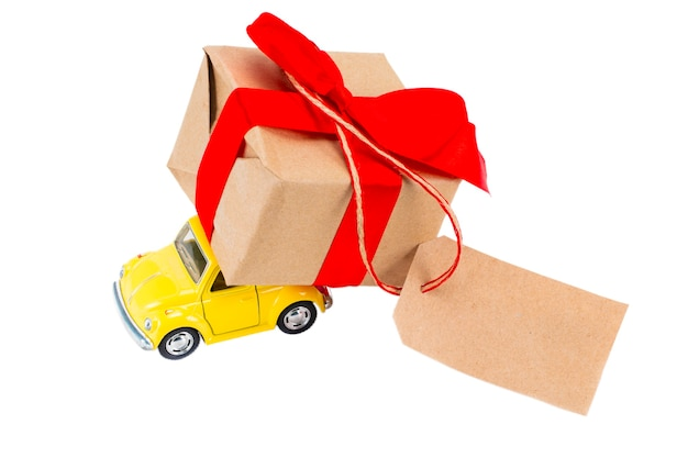 The yellow retro toy car delivering gifts box with tag with empty space for a text on white background.