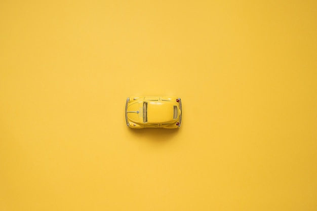 Yellow. retro toy car on yellow.. summer travel concept. taxi. top view.