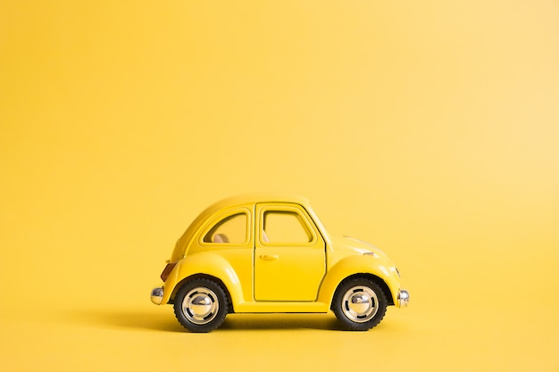 Yellow. retro toy car on yellow. summer travel concept. taxi