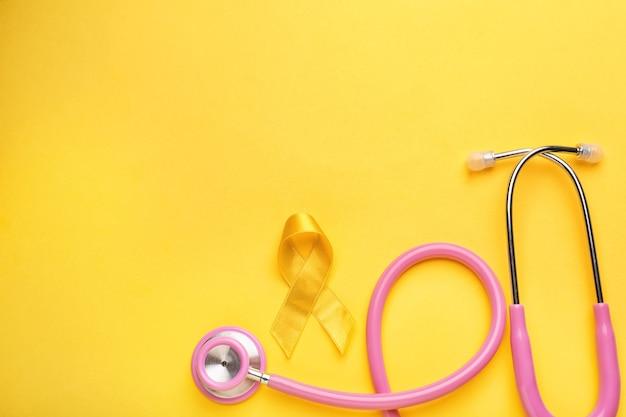Желтая лента и стетоскоп на цветной поверхности. концепция рака