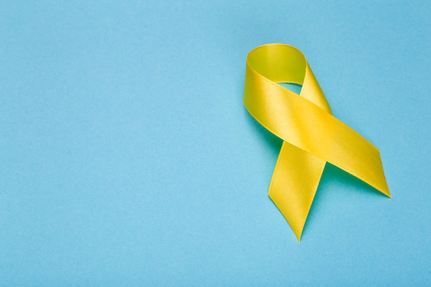 黄色いリボン、小児がん啓発月間。がんや自殺防止のリボン。子供の医療の背景。コピースペース