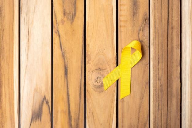 生きている人々と病気をサポートするための木製のテーブルの背景に黄色いリボン。 9月の自殺予防デー、小児がん啓発月間、世界対がんデーのコンセプト
