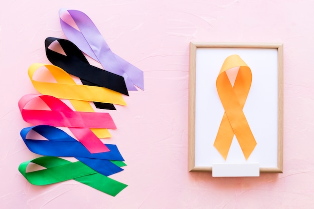 Yellow ribbon on white wooden frame near the row of colorful awareness ribbon