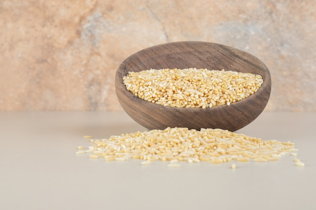 Yellow rice seeds in a wooden rustic cup on concrete.
